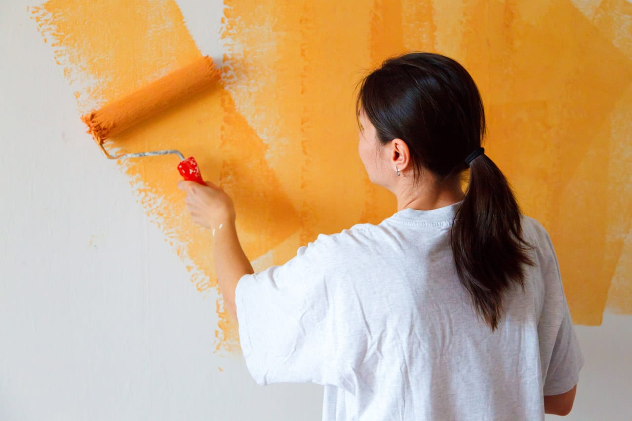 Woman painting a wall with orange paint