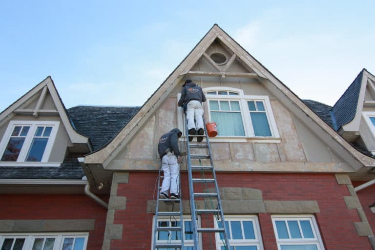 Two painters outside painting the exterior of a house.